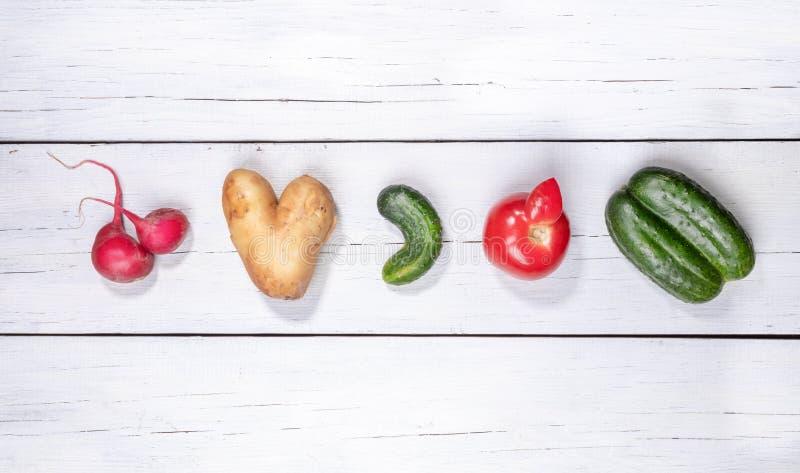 Stellen Sie von fünf hässlichem Gemüse ein: Kartoffel, Tomate, Gurke und Rettich breiteten in der Reihe auf weißem hölzernem Hint lizenzfreie stockfotos
