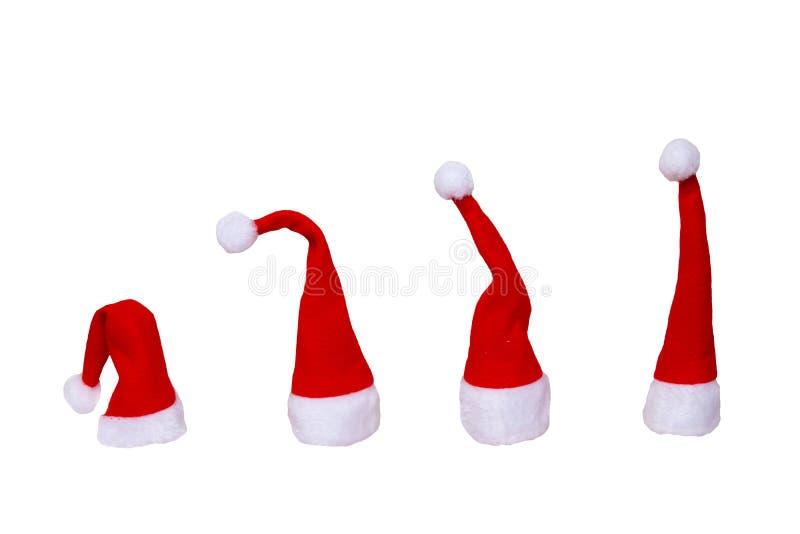 Stellen Sie von Santa Claus-Hüten ein, die auf einem weißen Hintergrund lokalisiert werden Weihnachtsdekorationen auf Blau lizenzfreies stockbild