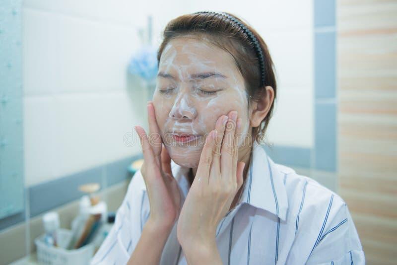 Stellen Sie waschendes Gesicht der Washington-Frau im Bad mit Schaumgummi gegenüber Schließen Sie oben von der jungen asiatischen lizenzfreie stockfotografie