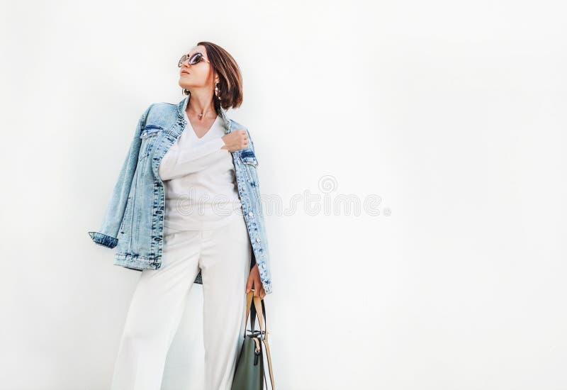 Stellende vrouw in elegante witte kleurenuitrusting met overmaats denim j stock afbeeldingen