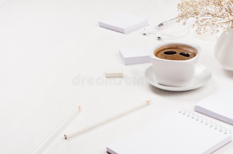 Stellte moderner einfacher Arbeitsplatz des Frühlinges des weißen Bürobriefpapiers mit Kaffeetasse, Blumen auf weißer hölzerner T lizenzfreies stockbild