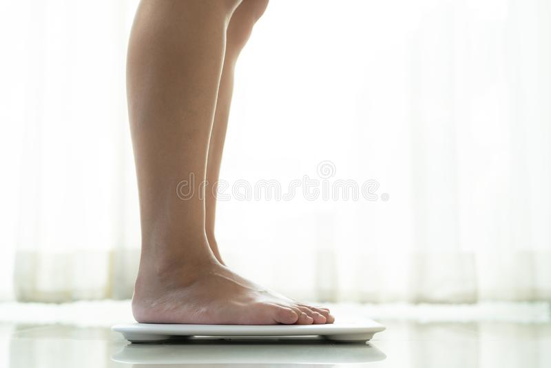 Stellung der jungen Frau auf digitaler Gewichtsskala lizenzfreies stockbild