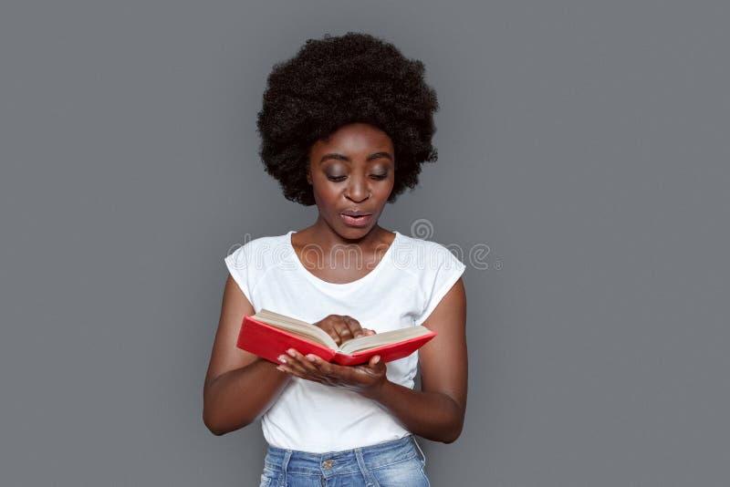Stellung der jungen Frau lokalisiert auf dem grauen Ablesenbuch neugierig stockbild