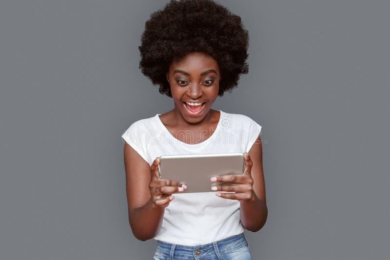 Stellung der jungen Frau lokalisiert auf Grau mit dem aufpassenden Videoschreien der digitalen Tablette aufgeregt stockbilder
