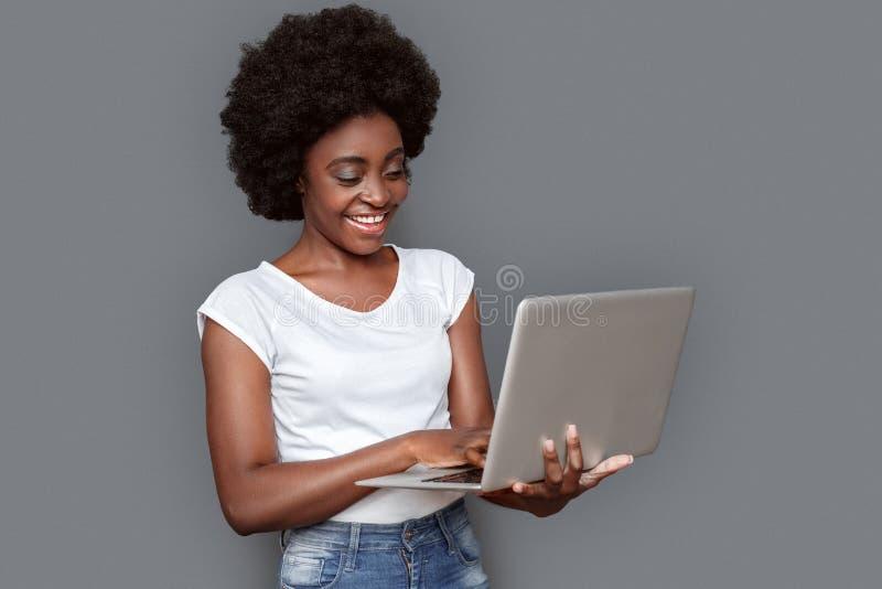 Stellung der jungen Frau lokalisiert auf Grau mit dem Laptopgraseninternet nett stockbild
