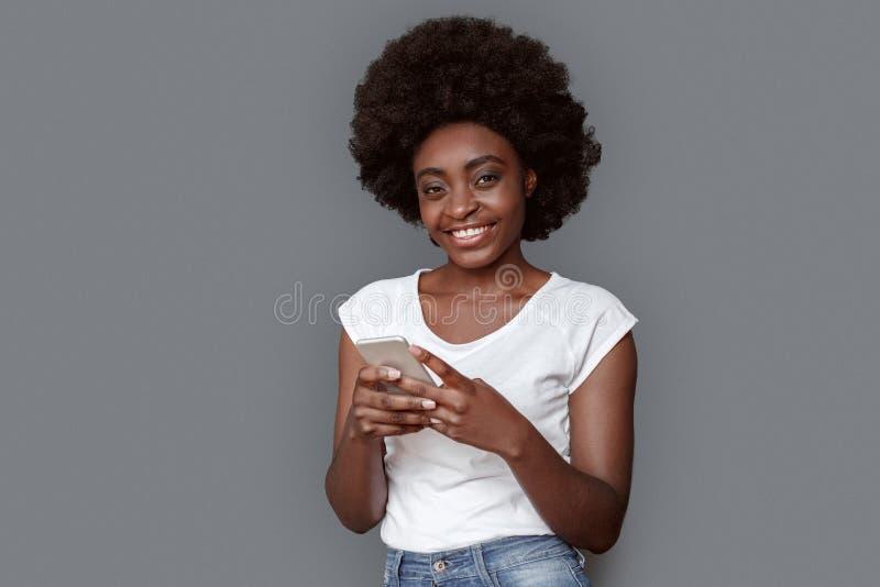 Stellung der jungen Frau lokalisiert auf Grau unter Verwendung des Smartphone, der die Kamera nett schaut stockfoto