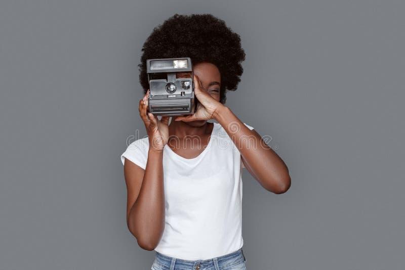 Stellung der jungen Frau lokalisiert auf grauen nehmenden Fotos auf polaroidkamera lizenzfreies stockbild