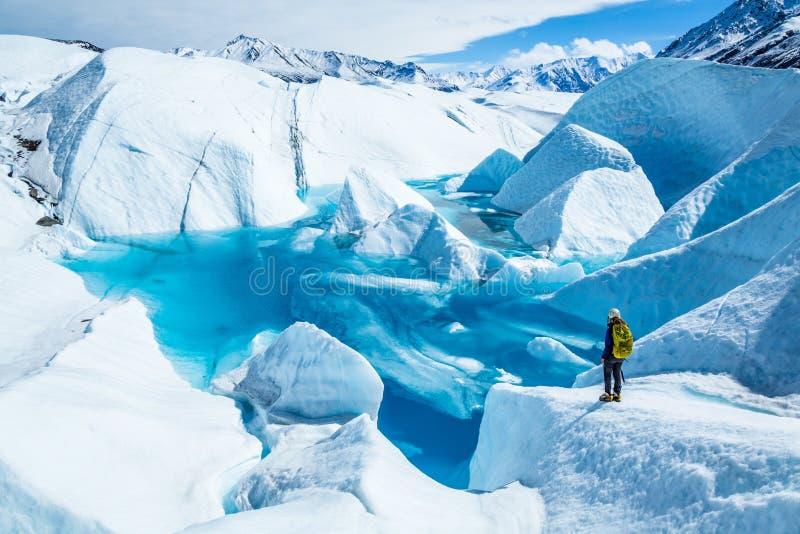 Stellung der jungen Frau nahe tiefem blauem See auf dem Matanuska-Gletscher in Alaska Sie trägt einen Rucksack und einen Sturzhel lizenzfreie stockfotos