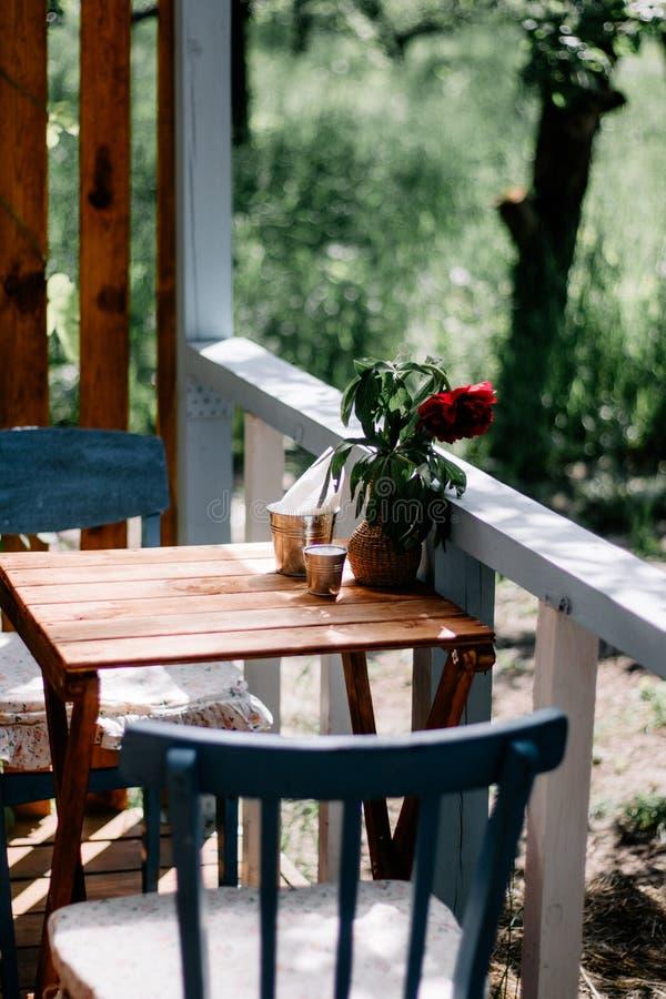 Stellung in der Straße auf einem Holztischvase mit einem Blumenstrauß von roten Pfingstrosen, Nahaufnahme lizenzfreies stockbild