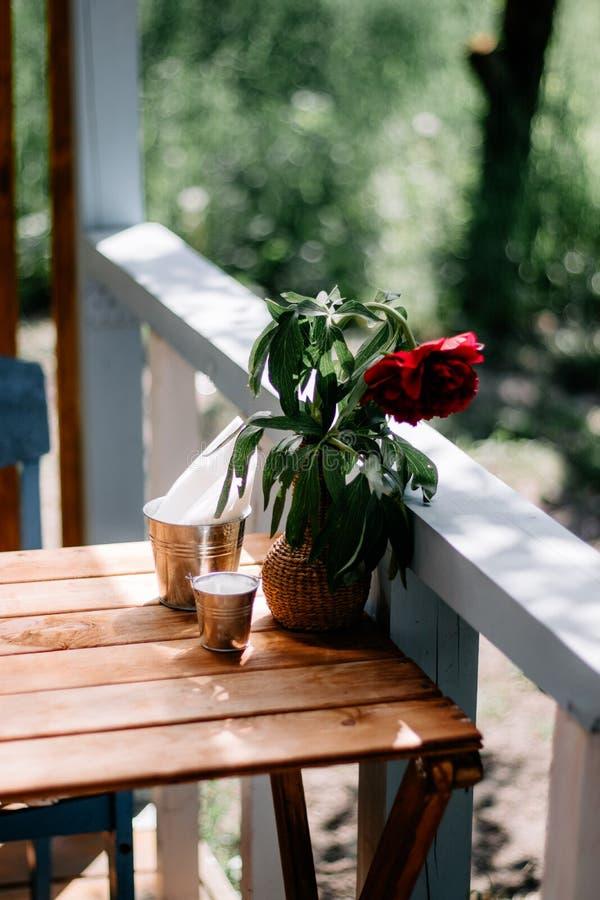 Stellung in der Stra?e auf einem Holztischvase mit einem Blumenstrau? von roten Pfingstrosen, Nahaufnahme stockfotos