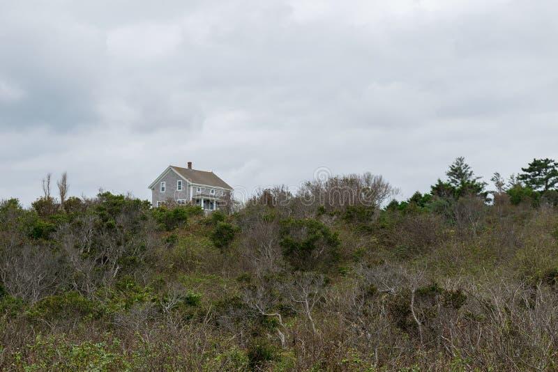 Stellung des abgelegenen Hauses an der Spitzenkante einer grünen herbstlichen Hügelseite, Block-Insel, RI lizenzfreie stockfotos