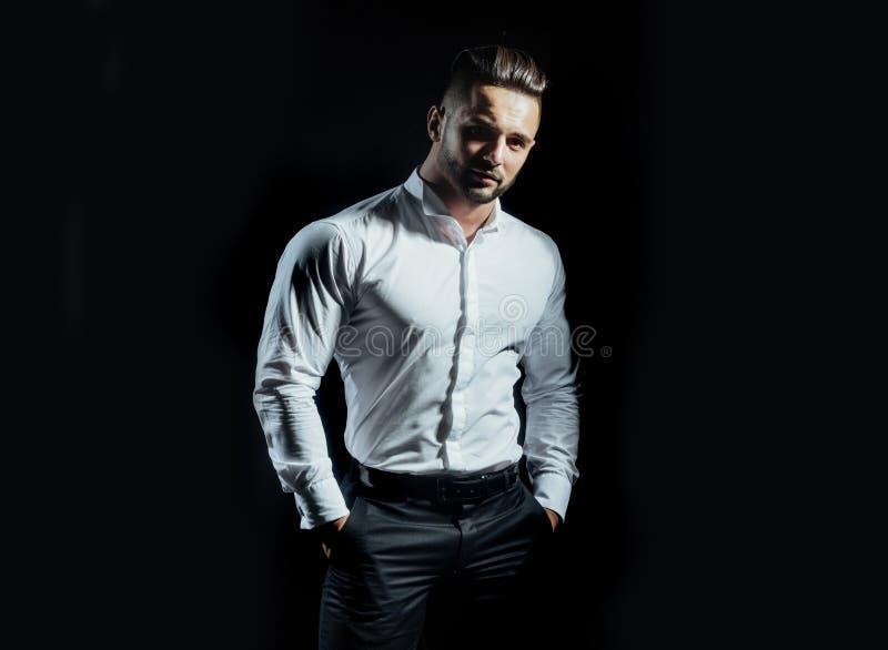 Stellung des gut aussehenden Mannes mit den Armen in den Taschen lokalisiert auf einem schwarzen Hintergrund Eine hübsche überzeu lizenzfreie stockfotografie