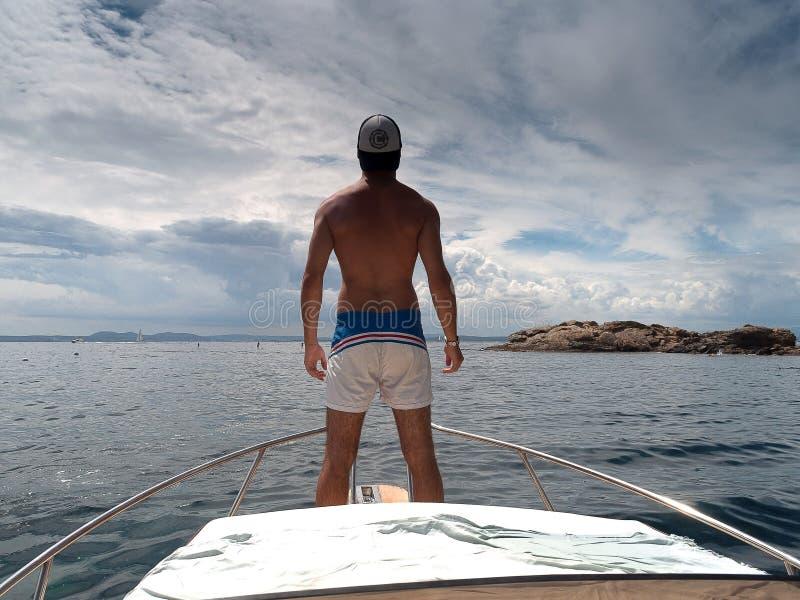 Stellung des jungen Mannes am Bootsbogen lizenzfreies stockfoto