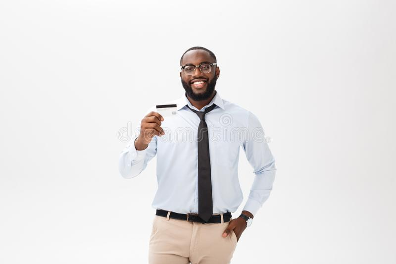 Stellung des jungen Mannes im Hemd zeigt Kreditkarte, betrachtet das Kameralächeln stockbilder