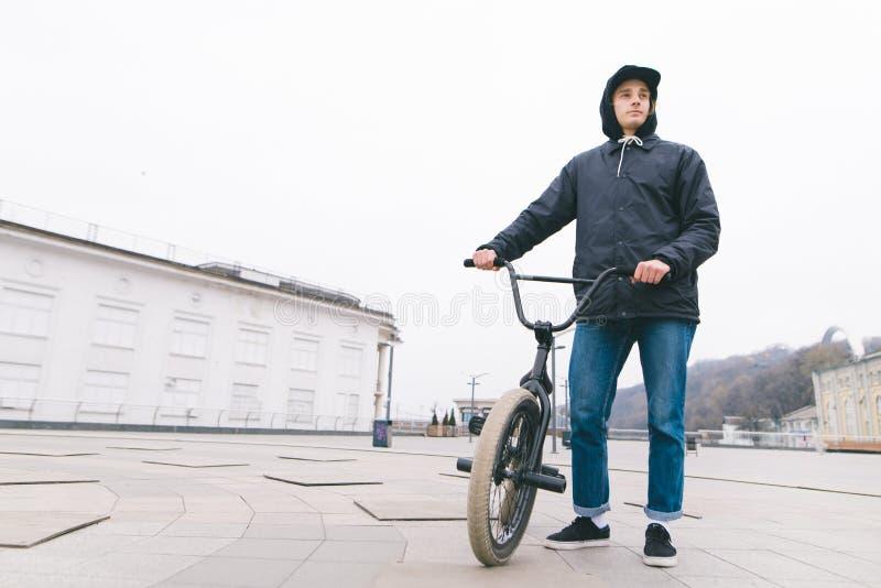 Stellung des jungen Mannes mit einem BMX-Fahrrad gegen den Stadthintergrund BMX-Reiter steht mit einem Fahrrad BMX-Konzept lizenzfreie stockfotografie