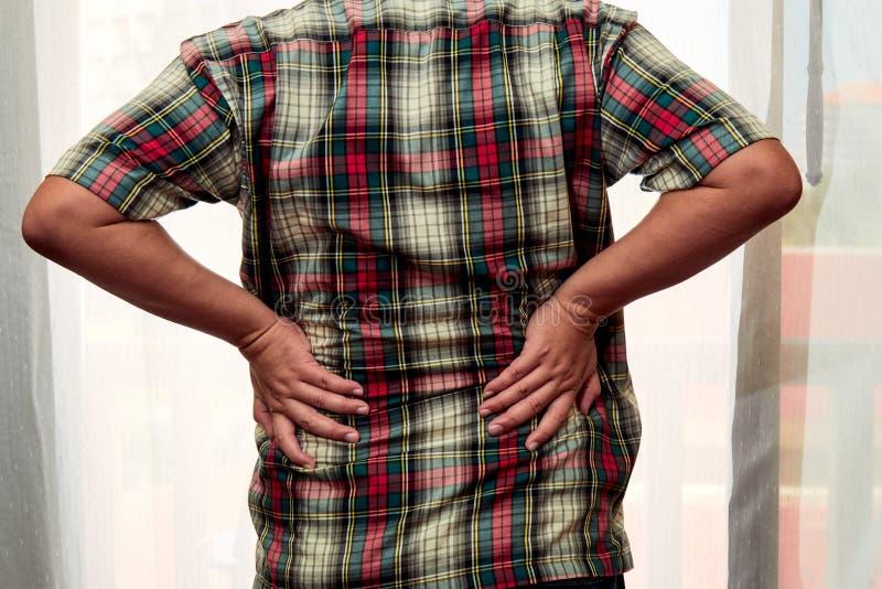 Stellung des Mannes 40s an der Tür und an erhaltenen Rückenschmerzen lizenzfreie stockfotos