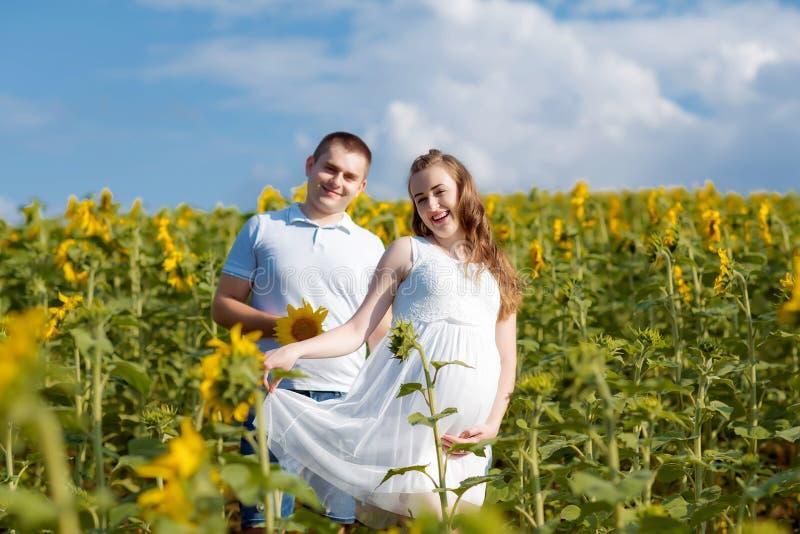 Stellung des Mannes und der schwangeren Frau auf einem Gebiet von Sonnenblumen Authentisches Lebensstil-Bild lizenzfreie stockfotos