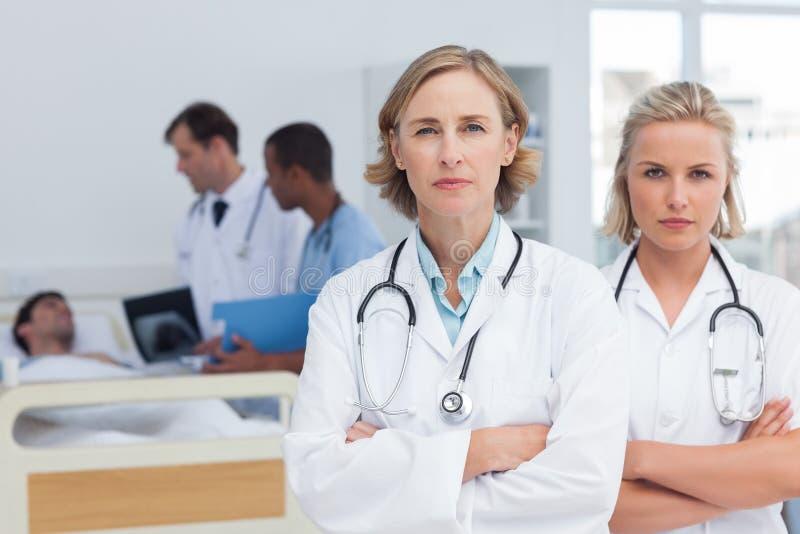 Stellung mit zwei ernste Frauendoktoren stockfoto