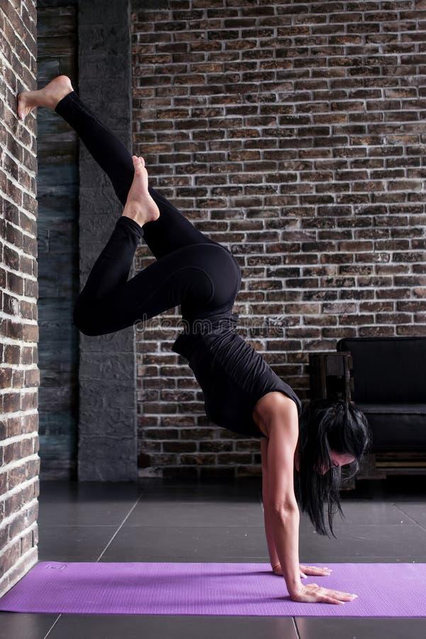 Stelt de begin vrouwelijke yogi die yogainversie uitoefenen status op handenbovenkant - onderaan het leunen tegen muur in geschik royalty-vrije stock afbeelding