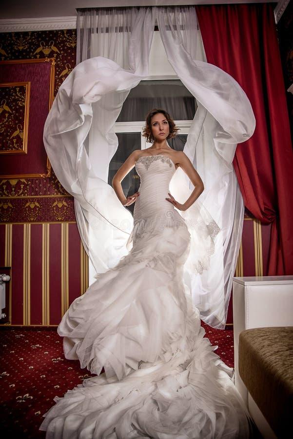 Stelt de de foto mooie bruid van de maniermode met krullend haar in een schitterende huwelijkskleding met kostbare perfect in ver stock foto's