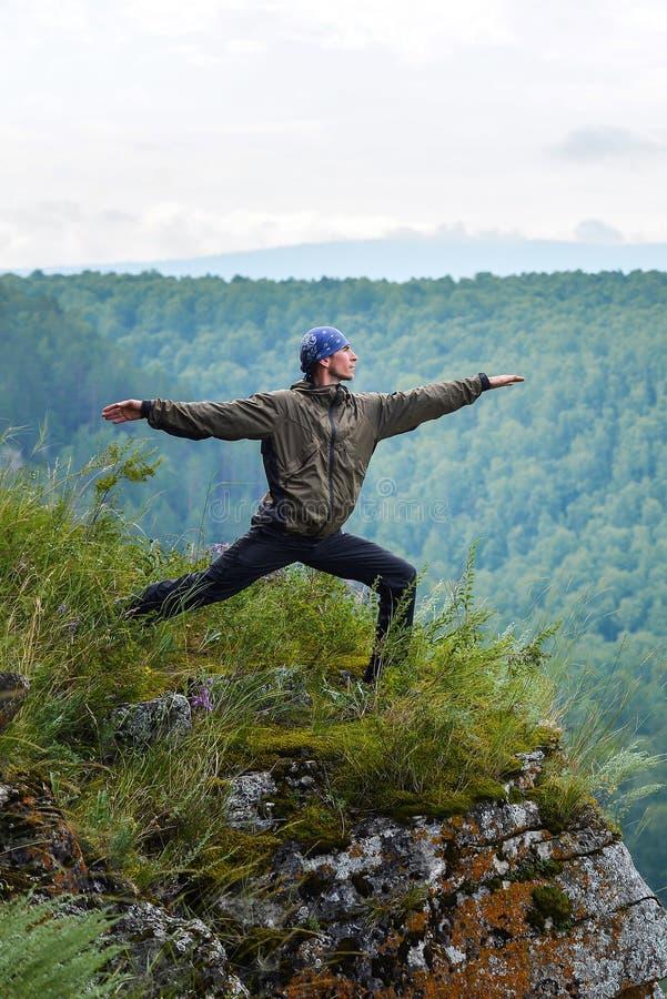 Stelt de praktizerende de yogastrijder van de mensenreiziger op de klip van berg stock fotografie