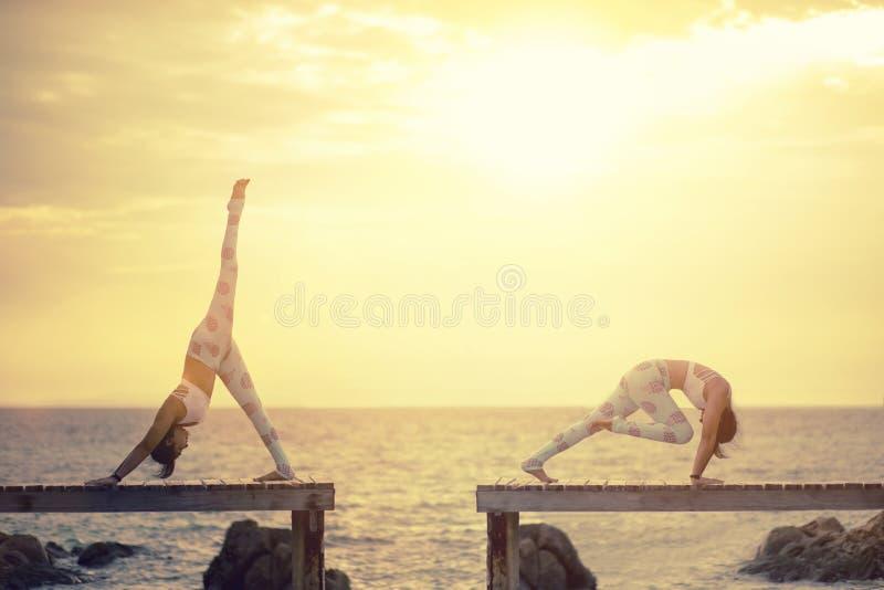 Stelt de twee vrouwen speelyoga op houten pijler tegen zon het toenemen ov stock fotografie