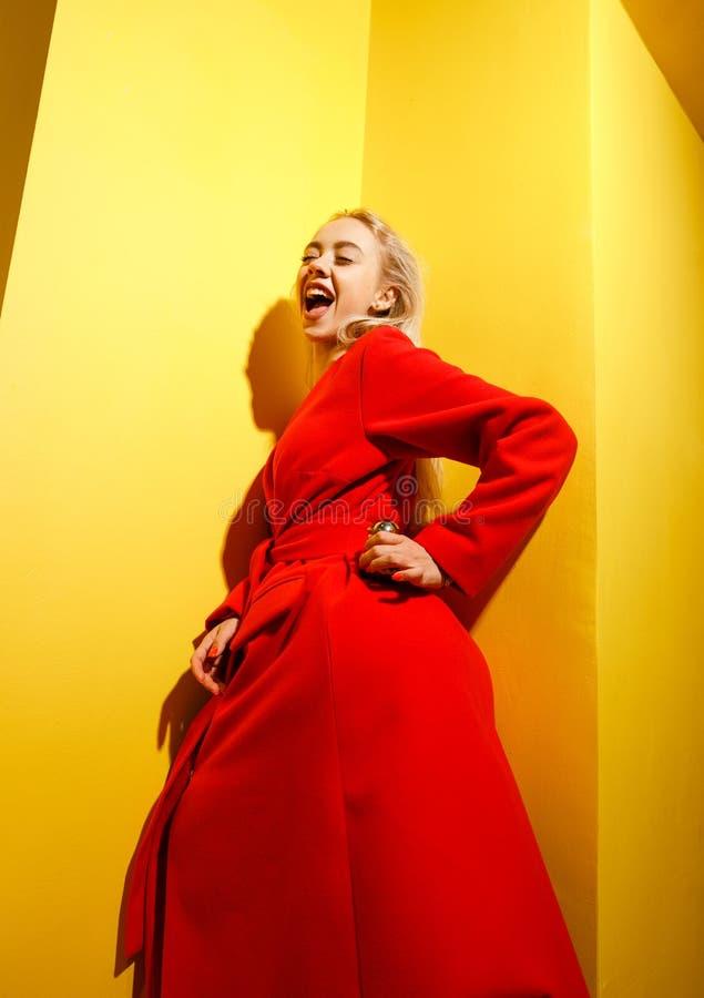 Stelt het manier jonge meisje blogger gekleed in modieuze rode laag met het goud weinig eendbeeldje in haar handen op royalty-vrije stock fotografie