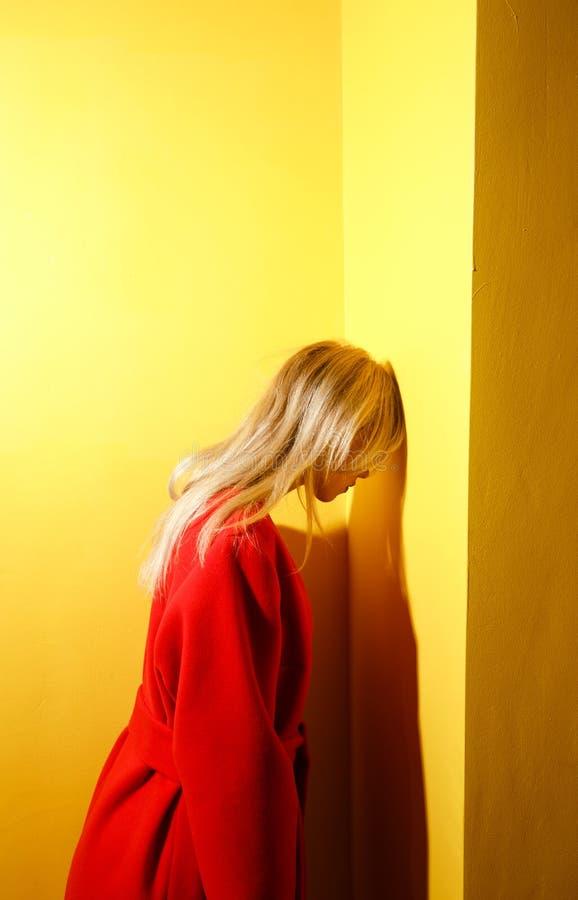 Stelt het manier jonge meisje blogger gekleed in modieuze rode laag op de achtergrond van gele muren in de showruimte royalty-vrije stock foto's