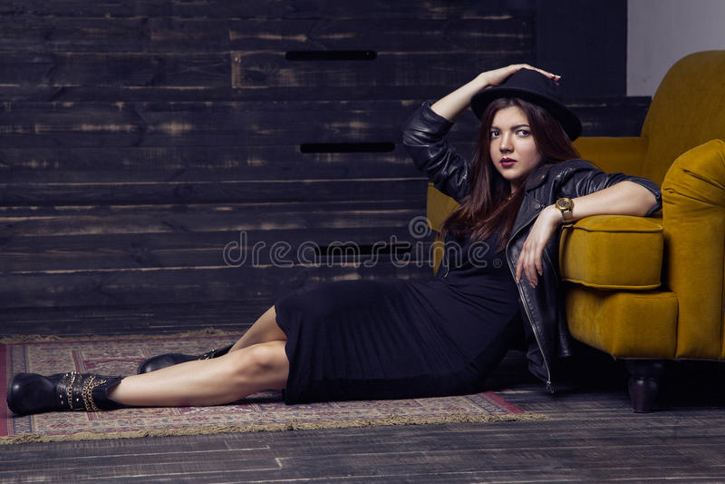 Stelt het manier mooie model van het Middenoosten met hipsterstijl op tapijt en gele bank stock fotografie