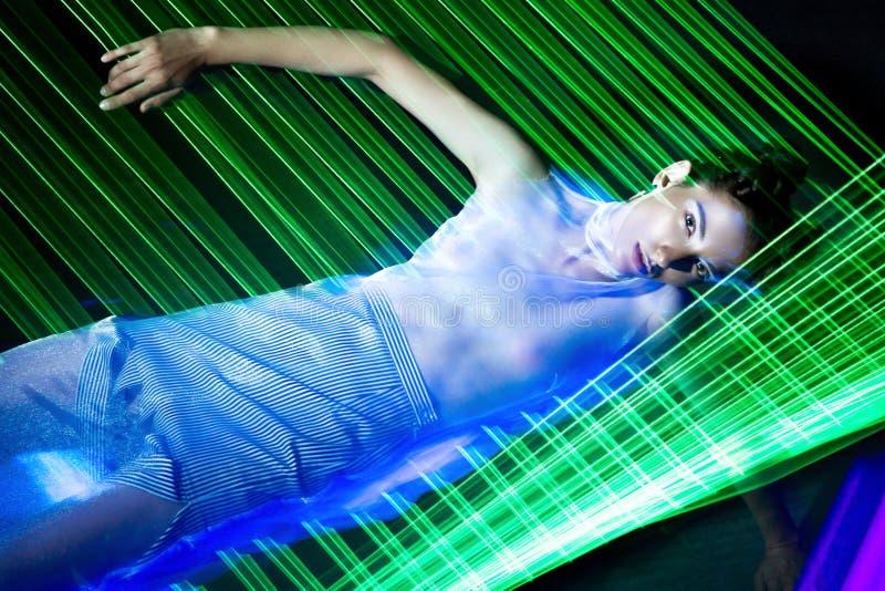 Stelt het mannequin mooie meisje in modieuze kleren in ultraviolet licht, verschillend tonen Schoonheidslichaam en gezicht royalty-vrije stock foto's