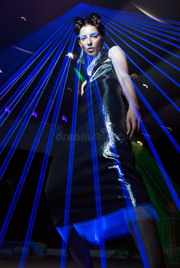 Stelt het mannequin mooie meisje in modieuze kleren in ultraviolet licht, verschillend tonen Schoonheidslichaam en gezicht stock fotografie