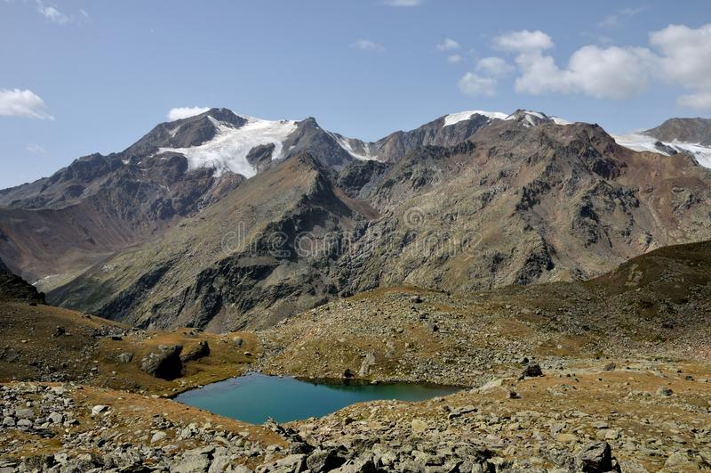 Stelvio parkerar, den blåa sjön och glaciären arkivbild