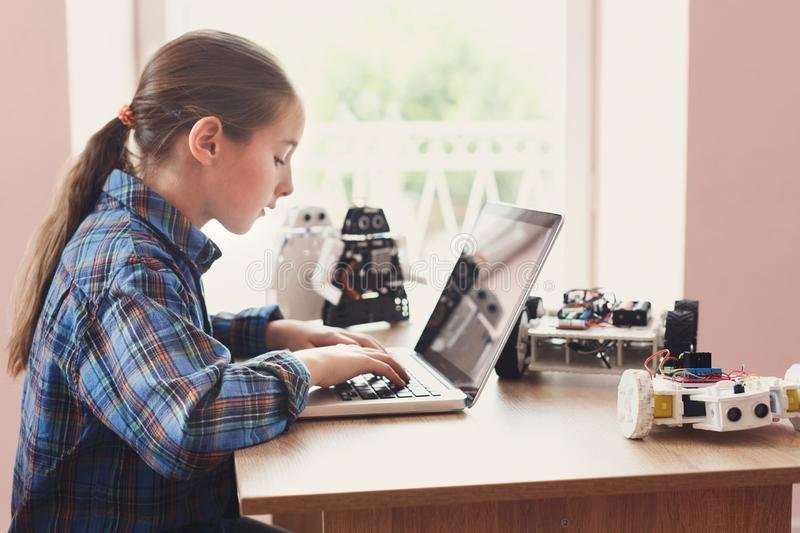 Stem education. Creating robotics project, mockup. Creating robotics project, mockup. Concentrated girl typing the plan of innovation robot model in laptop, diy royalty free stock photo