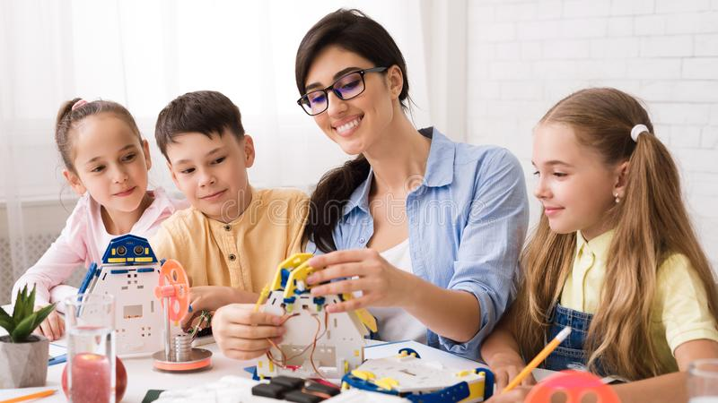 Stem education. Pupils creating robots with teacher stock photography