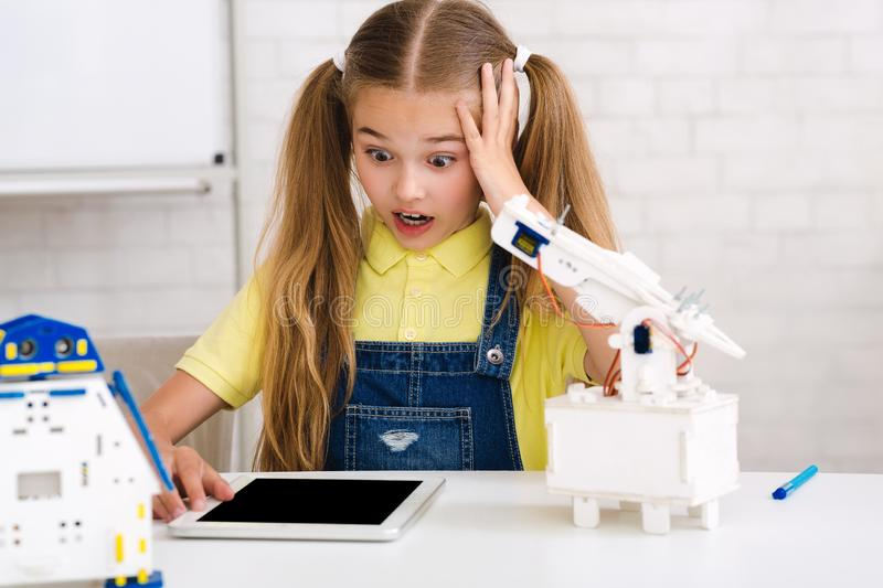 Stem education. Shocked girl made mistake when creating robot royalty free stock photography