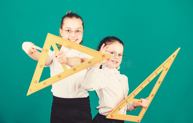 STEM school disciplines. small girls back to school. math lesson. Education and knowledge. Pupil cute girls with big. Rulers. School students learning geometry royalty free stock photo