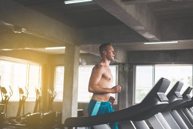 Stemde de sport knappe mens die op tredmolens lopen die cardio opleiding, Dwars geschikt lichaam doen en spier in de gymnastiek,  royalty-vrije stock foto