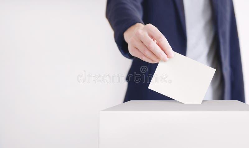 stemming Mens die een stemming zetten in een stemmingsdoos stock afbeeldingen