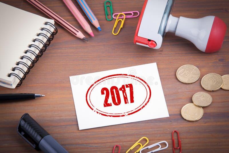Stempel 2017 Hölzerner Schreibtisch mit Briefpapier, Geld und einer Anmerkung stockfotografie