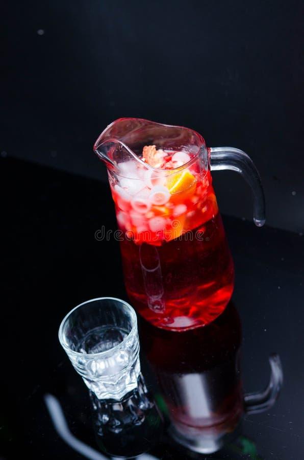 Stempel met vruchten en ijs in glazen en pincher Eigengemaakte verfrissende fruitsangria over rustieke houten lijst, stock afbeelding