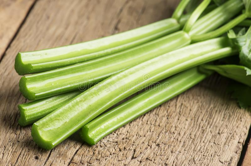 Stems of fresh celery with leaves on the table, vintage wooden kitchen table background, selective focus stock image