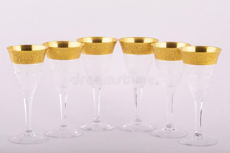 Stemware facettierte die Gläser, die vom tschechischen Glas mit einer goldenen Verzierung gemacht wurden, die auf einem weißen Hi lizenzfreies stockbild