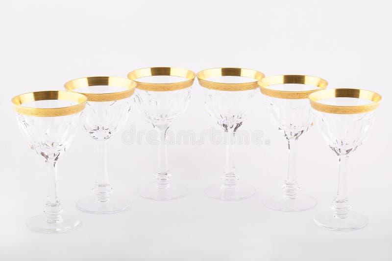 Stemware facettierte die Gläser, die vom tschechischen Glas mit einer goldenen Verzierung gemacht wurden, die auf einem weißen Hi lizenzfreie stockfotos
