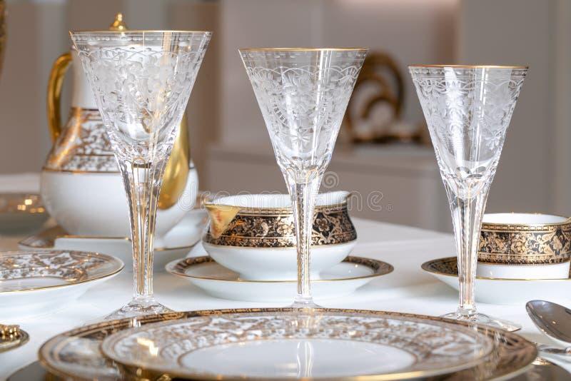 Stemware facettierte die Gläser, die vom tschechischen Glas mit goldene Linien und Muster auf dem Hintergrund einer weißen Teekan lizenzfreie stockfotos