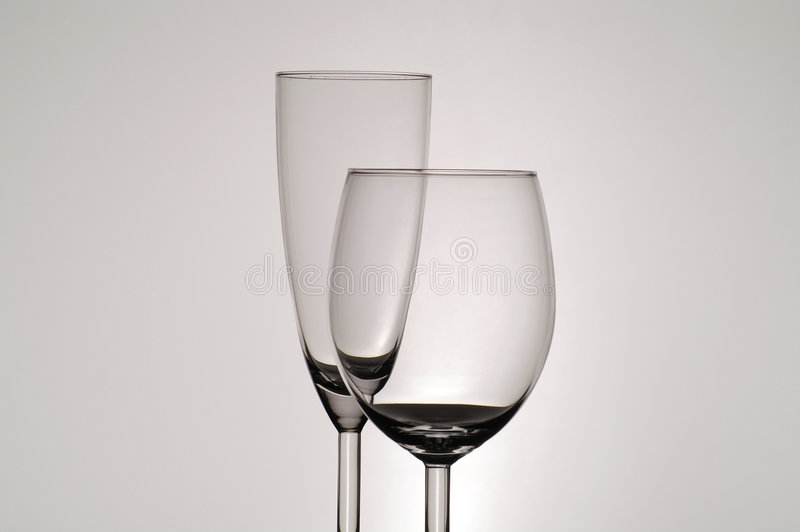 Stemware Glasses. Two different shaped clear stemware glasses, the shorter of the two in front of the other. Isolated against a gray background stock photos