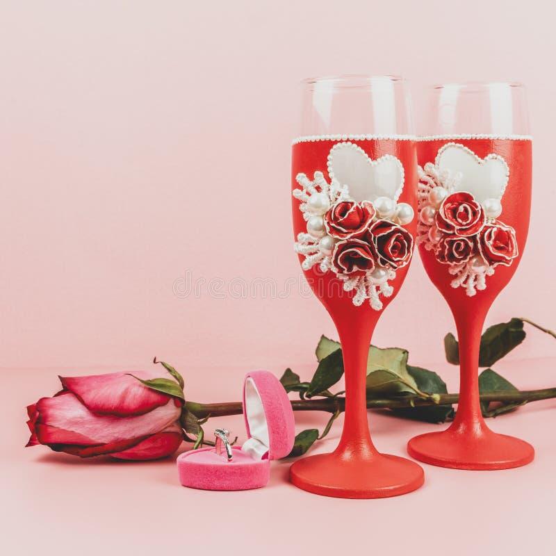 Stemware, Ring im Kasten und Rose auf rosa Hintergrund Dekorative verzierte Weingläser lizenzfreie stockfotos