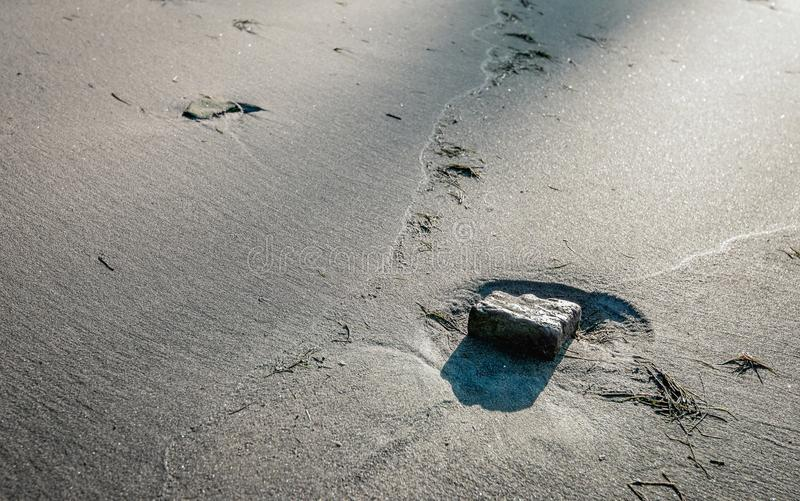 Sten i en skrattgrop på stranden royaltyfria bilder
