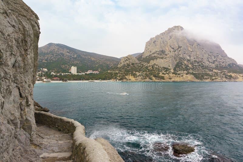 Sten-stenlagd Golitsyn slinga i semesterortbyn av Novy Svet och kust- klippor i Krimet molnig dag arkivbilder