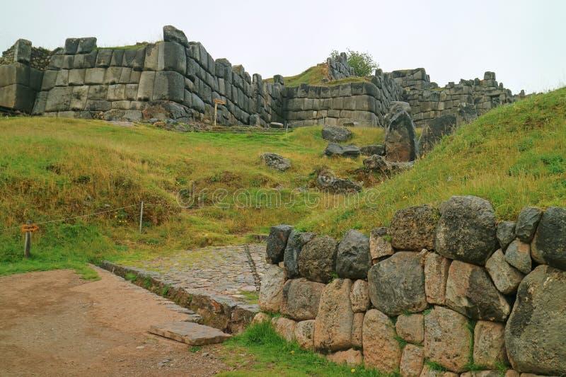 Sten stenlagd väg till solporten INTIPUNKU som är skriftlig på vägvisaren av den Sacsayhuaman Incascitadellen på bergstoppet av C arkivbild