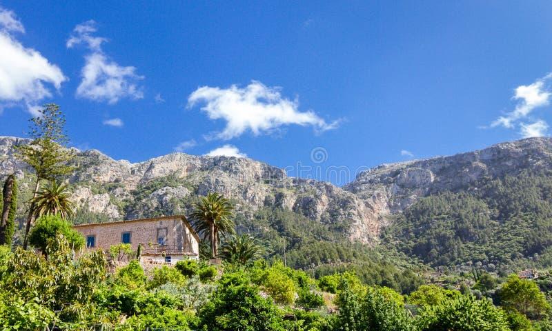 Stena huset med den frodiga trädgården i Mallorca med bergsikt royaltyfri bild